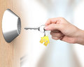 Hand holding key with house shape key ring to unlock aisle background Royalty Free Stock Images