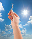 Hand holding key on sunny sky background Stock Photo