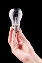 Hand holding light bulb isolated on black Royalty Free Stock Photo