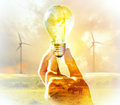 Hand holding light bulb on wind turbine Royalty Free Stock Photo