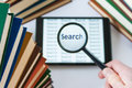 Hand holding a magnifying glass over a tablet surrounded by book Royalty Free Stock Photo