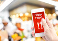 Hand holding mobile with Order food online with blur restaurant Royalty Free Stock Photo