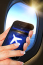 Hand holding mobile phone with flight mode in the airplane closeup of Royalty Free Stock Images
