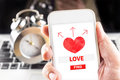 Hand holding mobile with red heart and find love word on screen