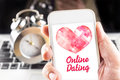 Hand holding mobile with red heart and online dating word on scr