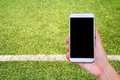 Hand holding mobile smart phone with football stadium screen. Royalty Free Stock Photo