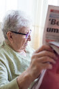 Hand holding newspaper a senior person reading close up Royalty Free Stock Images