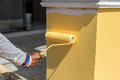 Hand holding paint roller and painting to the wall Royalty Free Stock Photo