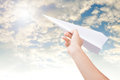 Hand holding paper plane toward cloudy blue sky. Royalty Free Stock Photo