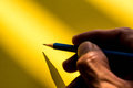 Hand holding pencil to write on the paper in shadow Royalty Free Stock Photo