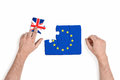 Hand holding piece of jigsaw puzzle with European Union and Great Britain flag isolated on white background Royalty Free Stock Photo