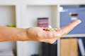 Hand holding pills many colorful in their palm Royalty Free Stock Image