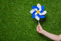 Hand holding pinwheel over green grass Royalty Free Stock Photo