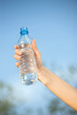 Hand holding plasic bottle of water plastic in front sky Stock Photography