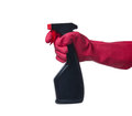 Hand holding plastic spray bottle with red latex glove on white background Royalty Free Stock Image