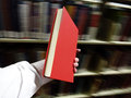 Hand holding red book in library hands a with background Stock Photography
