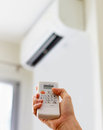 Hand holding remote control, adjusting temperature of air conditioner mounted on a white wall. Indooor comfort temperature. Royalty Free Stock Photo