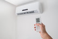 Hand holding remote control for air conditioner on white wall. Royalty Free Stock Photo