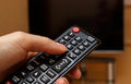 Hand holding remote control for television, choosing channel in TV Royalty Free Stock Photo