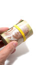 Hand holding a roll of dollars canadian with yellow plastic band over the eyes Royalty Free Stock Images
