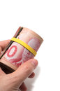 Hand holding a roll of dollars canadian with yellow plastic band over the eyes Royalty Free Stock Photography