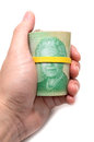 Hand holding a roll of dollars canadian with yellow plastic band over the eyes the queen elizabeth Royalty Free Stock Photography