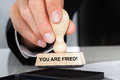 Hand Holding Rubber Stamp With You Are Fired Sign Royalty Free Stock Photo