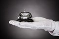 Hand holding service bell close up of with white gloves Royalty Free Stock Photo