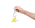 Hand holding silver key with golden pound symbol shape keyring Royalty Free Stock Photo