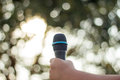 hand holding a single microphone against colourful background,si Royalty Free Stock Photo