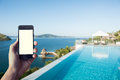 Hand holding smart-phone for booking hotel with coron island background Royalty Free Stock Photo