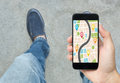 Hand holding smart phone with map gps navigation application.