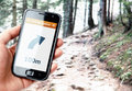 Hand holding smartphone with gps navigation on the screen in the forest Stock Photo