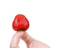 Hand holding a strawberry whte background Royalty Free Stock Images