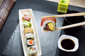 Hand holding sushi roll using chopsticks Royalty Free Stock Photo