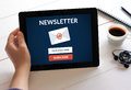 Hand holding tablet with subscribe newsletter concept on screen.