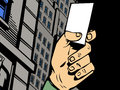 Hand holding a ticket comic book style illustrated blank in dark city Stock Photo