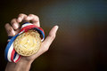 Hand holding up a gold medal Royalty Free Stock Photo