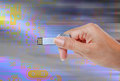 Hand holding USB data storage against light and circuit Royalty Free Stock Photo