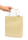 Hand holding a white box in brown paper shopping bag Royalty Free Stock Photo