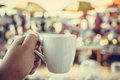 Hand holding white coffee cup on fresh food maket background Stock Photo