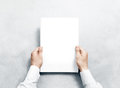 Hand holding white journal with blank cover mockup. Royalty Free Stock Photo
