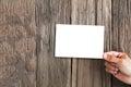 Hand holding white photo frame on vintage grunge wooden background Royalty Free Stock Photo
