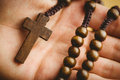 Hand holding wooden rosary beads Royalty Free Stock Photo