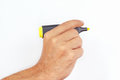 Hand holding a yellow marker on white background Royalty Free Stock Photo