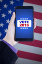 Hand holds cellphone with vote button image of holding mobile phone on the screen shot american flag background Stock Image