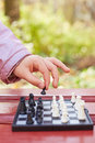 Hand holds chess piece above chessboard while game child in park outdoors Royalty Free Stock Image