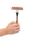 Hand holds grilled sausage on fork isolated a white background Stock Photo