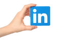 Hand holds Linkedin logo sign printed on paper on white background Royalty Free Stock Photo