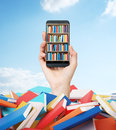 A hand holds a smartphone with a book shelf on the screen. A heap of colourful books. A concept of education and technology.Cloudy